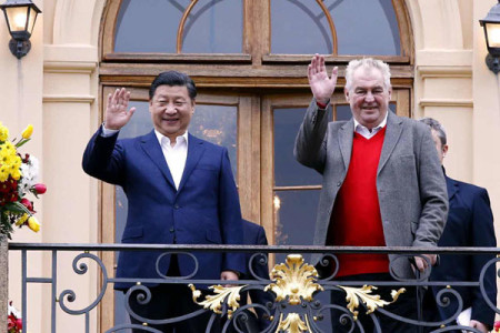 Visiting Chinese President Xi Jinping, left, and Czech President Milos Zeman wave to the press before holding an informal meeting at the Lany chateau, the host's private residence
